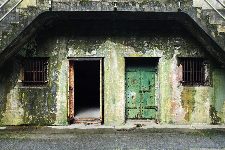 Open and closed rusty green steel doors in concrete bunker tunnels, Artillery Hill, Fort Worden State Park, Port Townsend, Washington, USA