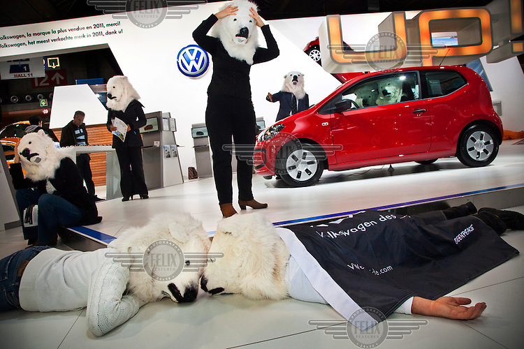Campaigners for Greenpeace, dressed in polar bear costumes, at a car show in Brussels. They are protesting against the carmaker VW (Volkswagen) which is opposing a new EU law to limit CO2 emissions.