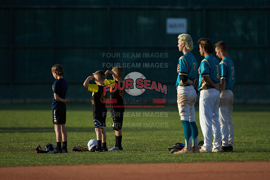 Young baseball players salute the flag as they take the field for the National Anthem with Mooresville Spinners players (L-R) Kye Andress (7) (Catawba Valley CC), Anthony Hennings (3) (Elon), and Justin Fox (2) (Erskine College) prior to the game against the Concord A's at Moor Park on July 31, 2020 in Mooresville, NC. The Spinners defeated the Athletics 6-3 in a game called after 6 innings due to rain. (Brian Westerholt/Four Seam Images)