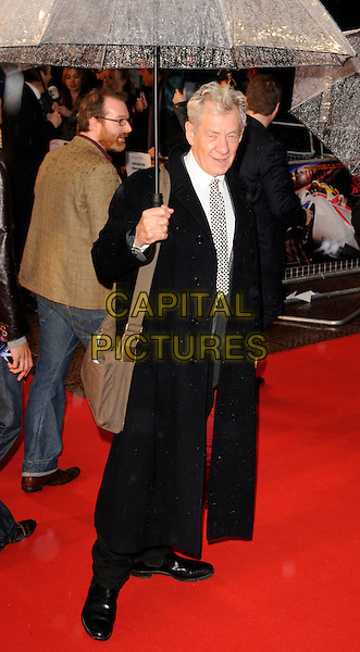 "SIR IAN McKELLEN.""Speed Racer"" UK film premiere at the Empire, Leicester Square, London, England..April 29th,  2008.full length black coat white check tie umbrella raining mckellan brown bag satchel .CAP/CAN.©Can Nguyen/Capital Pictures."