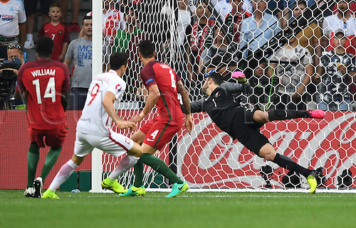 30.06.2016. Marseille, France.  Robert Lewandowski of Poland scores the goal for a 1-0 lead against goalkeeper Rui Patricio (R) , William Carvalho (L) and Jose Fonte (2-R) of Portugal during the UEFA EURO 2016 quarter final soccer match between Poland and Portugal at the Stade Velodrome in Marseille, France, 30 June 2016