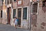 A woman walking down a street in Venice, Italy