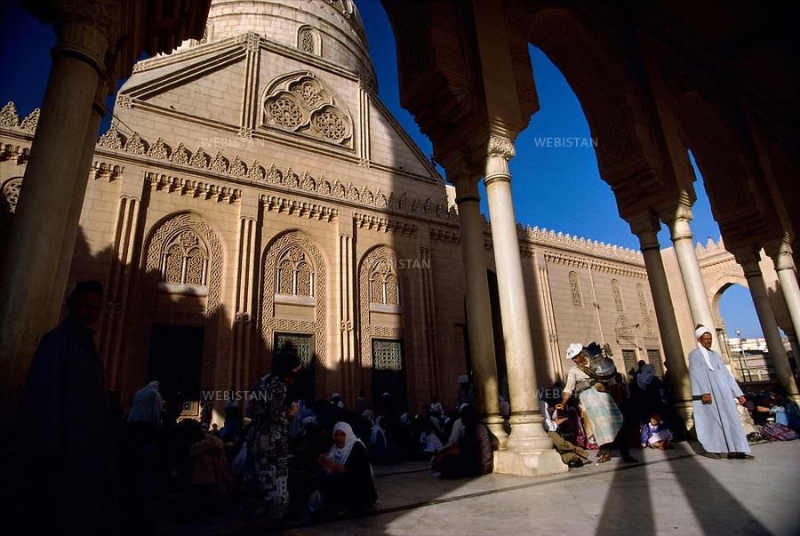 "Egypt. Near Tanta. May 1996. During the ""mouled"" (prophet's bithday) of Tanta. Pepole pass by Tanta's mosque, built in the middle of the 19th century. .It is the place of the mausoleum of the greatest Muslim saint of the country, Sidi Ahmad el-Badaoui..Egypte. Pres de Tanta. Mai 1996. Pendant le ""mouled"" (anniversaire du Prophete) de Tanta. Des gens passent devant la mosquee actuelle de Tanta, construite a la moitie du XIXe siecle. .Elle abrite le mausolee du plus grand saint musulman du pays: Sidi Ahmad el-Badaoui.."