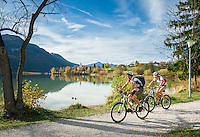 Germany, Bavaria, Swabia, East-Allgaeu, Fuessen: district Weissensee-Oberkirch at Lake Weissensee with parish church St. Walburga, two women on a cycling trip in autumn | Deutschland, Bayern, Schwaben, Ost-Allgaeu, Fuessen: Ortsteil Weissensee-Oberkirch am Weissensee mit Pfarrkirche St. Walburga, zwei Frauen machen eine Radtour im Herbst