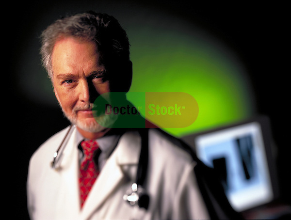 portrait of smiling doctor with monitor in background