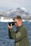 A man photographs the icebergs and landscape of Eastern Greenland. The man is a scientist with the Cape Farewell Youth Expedition that was organized by the British Council of Canada.