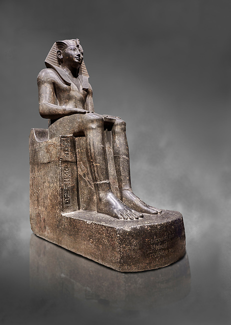 Ancient Egyptian statue of Tuthmosis II, granodorite, New Kingdom, 18th Dynasty, (1479-1425 BC), Karnak, Temple of Amun. Egyptian Museum, Turin. Grey background.<br /> <br /> Tuthmosis II is shown wearing Royal regalia including the shendyt kilt, the nemes headdress and the uraeus cobra on his forehead. Between his legs in a bulls tail, the symbol of power. On the sides of the throne is the sema-tawy, a sign composed of a lotus and papyrus, the symbols od Upper and Lower Egypt. Under the feet of the king are the Nine Bows, the enemies of Egypt. Together these symbolise that the pharaoh keeps the two halves of Egypt together and protects them against her enemies. Drovetti Collection. C 1376