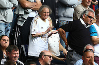 An elderly Swansea City fan cheers their team on during the Barclays Premier League match between Swansea City and Manchester City played at The Liberty Stadium, Swansea on 15th May 2016