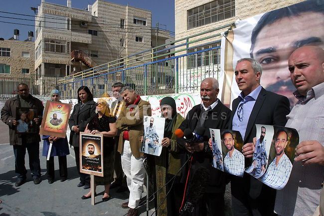 Layla Issawi holds a picture of her son Samer Issawi, a Palestinian held in Israeli jail and on hunger strike for more than 200 days, alongside her husband Tareq and European politicians of the Council for European Palestinian Relations Sandra White and Jim Hume from Scotland, Niccolo Rinaldi from Italy, Gerald Kaufman of Britain, Pat Sheehan of Ireland and Pauline McNeill of Scotland on March 2, 2013. The European lawmakers were in the region in a show of support for Palestinian detainees on hunger strike in Israeli prisons. Photo by Mahfouz Abu Turk
