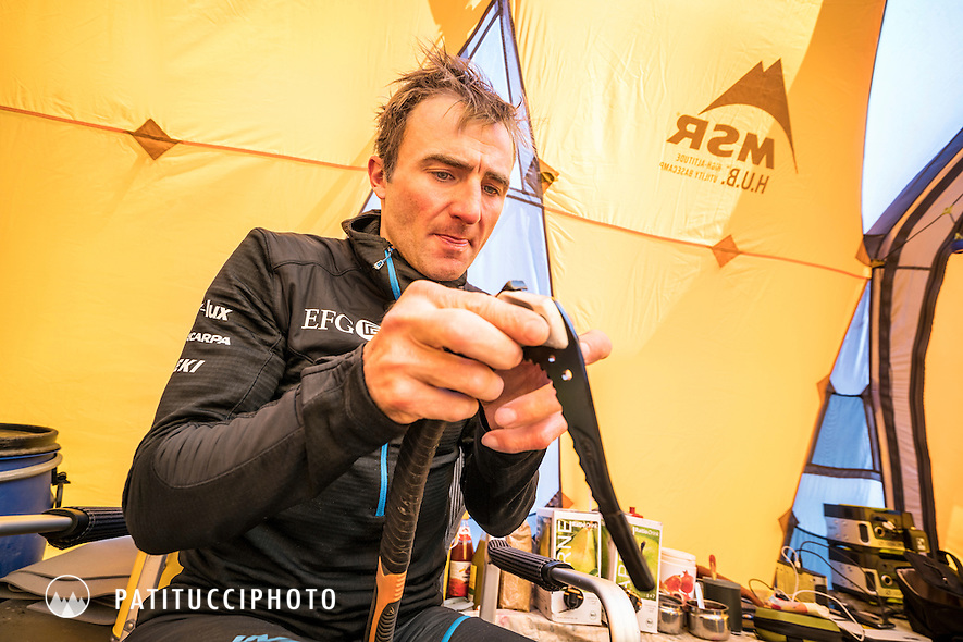 Ueli Steck working on his ice axe inside a basecamp tent during his climbing expedition to the 8000 meter peak Shishapangma, Tibet