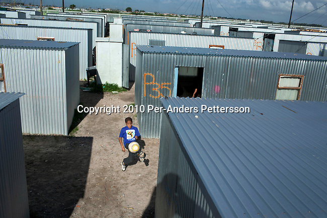 """CAPE TOWN, SOUTH AFRICA - MAY 3: An unidentified boy practice soccer between tin shacks on May 3, 2010, in Blikkiesdorp about 40 kilometers south of Cape Town, South Africa. Blikkiesdorp, which is Afrikaans for """"Tin Can Town"""", was given its name by its residents because of the row-upon-row of tin-like shacks made of corrugated iron. It was built by the City of Cape Town in 1997 and about 1600 one-roomed shacks were built. It has been known for its bad conditions and a dumping ground for shack dwellers from other areas around Cape Town. Recently many street people in Cape Town has been forcefully removed and relocated to this place. The ones that have refused has been put in holdings cells or prisons such as Pollsmoor Prison. This campaign has  identified in the preparation for the soccer World Cup, who starts on June 11, 2010 and goes on for a month. The City of Cape Town doesn't want international visitors to be hassled by street people. (Photo by Per-Anders Pettersson)"""