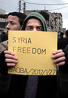 A protestor holds up a handwritten sign that reads: 'Syria Freedom' during the funeral of Mazen Abu Dahab in the Sakba district of Damascus. He was reported to have been shot by security forces. Sakba is a suburb of Damascus that has been one of the main centres of anti-regime activity.