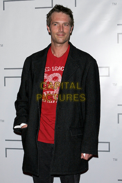 MICHAEL VARTAN.PSP North American Launch Party held at the Pacific Design Center, West Hollywood, CA..March 14th, 2005.Photo Credit: Jacqui Wong/AdMedia.half length black coat jacket hand in pocket white plastic bracelet red dragon t shirt logo slogan.www.capitalpictures.com.sales@capitalpictures.com.© Capital Pictures.