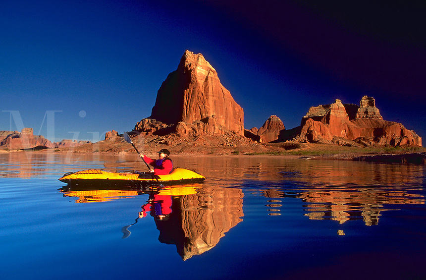 Woman in a yellow kayak paddling past Padres Buttes on Lake Powell in Arizona.