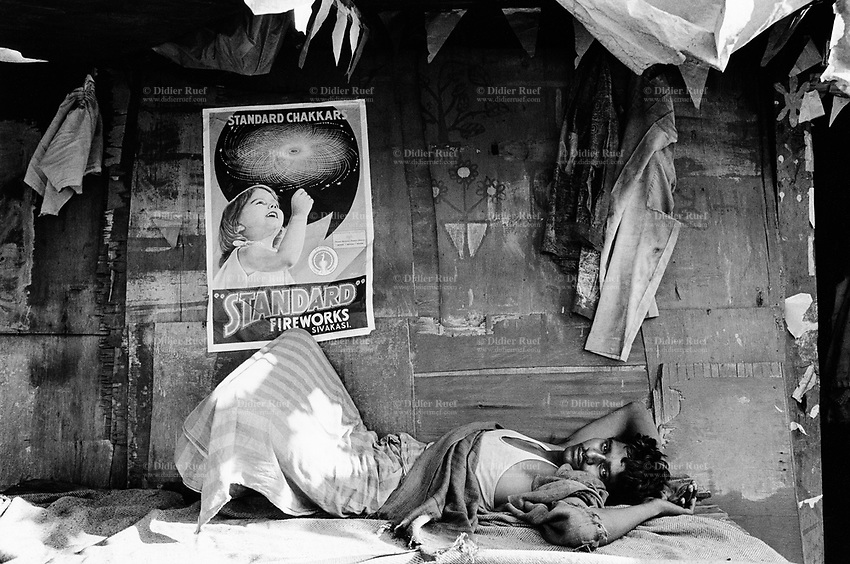 "India. Province of Gujarat. Alang. A worker, a sick man suffering from malaria, lays on his back and rests on a bench on the doorstep of his wood house. A poster for the "" Standard Fireworks"" brand shows a girl using a firework. The advertisement is taped on the wall. Alang, located in the Gulf of Khambhat, is a ships breaking place and is considered as the biggest scrapyard in the world. © 1992 Didier Ruef"