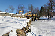 Old North Bridge at Minute Man National Historical Park in Concord, Massachusetts during the winter months. This footbridge spans the Concord River, and it is the site of a Revolutionary War Battlefield (on April 19, 1775, battle of Concord, which marks the beginning of the American Revolutionary War).
