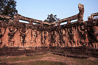 The Terrace of the Leper King is in the  Royal Square of Angkor Thom.  It was built in the Bayon style under Jayavarman VII, though its modern name derives from a 15th century sculpture discovered at the site. The statue depicts the Hindu god Yama, the god of Death. He was called the Leper King because discoloration and moss growing on the original statue was reminiscent of a person with leprosy, and also because it fit in with a Cambodian legend of an Angkorian king who had leprosy.