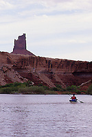 Solitary paddler and towering sandstone butte tower, Green River, Canyonlands National Park, Utah