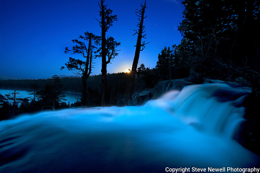 """Blue Moon"" Eagle Falls- Emerald Bay Lake Tahoe, CA. This is a full moon rising over the Lake Tahoe Basin on May 5th, 2012. This image was taken at 8:37pm.  I used a 30 second exposure, f8.0 aperture , ISO 400, 16mm lens.  It was my first time using my Canon 5D Mark ll and I wanted to capture the moon lighting up the basin with the water in motion using a longer exposure. I set my wide-angle lens at 16mm to capture Eagle Falls and Fannette Island in Emerald Bay.  In Lake Tahoe Emerald Bay is the most photographed location. You can find many different photographs of the sunrise with Lower Eagle Falls in the foreground that have Fannette Island included along with the sun rising over the ridge in the background. So I went out and shot a Full Moon rising over the waterfall.  I used a 30 second long exposure to capture the available light in the area and it gave the water a milky flowing in motion look.  The Sun had just set and the Moon was just rising so the sky was still incredibly blue.  With the shutter open for 30 seconds it allowed the color of the sky to reflect on the water giving it the blue tint.  Fannette Island can be seen down in Emerald Bay in the middle of the photo on the left side.  The detail is so good you can see the reflection of the trees in the water that are located on the waters edge down in Emerald Bay. Stars can be seen in the sky, car lights on Emerald Bay road and house lights on Kingsbury Grade."