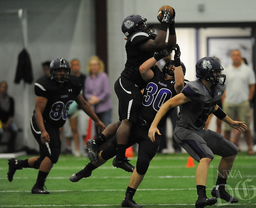 NWA Democrat-Gazette/ANDY SHUPE<br /> Rashad Brown (top) of Fayetteville intercepts a tipped ball Friday, May 29, 2015, during the Bulldogs' annual Spring Game inside the school's indoor facility in Fayetteville. Visit nwadg.com/photos to see more photographs from the game.