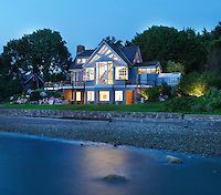 The modern glass-fronted house all lit up at dusk and seen from across the shoreline