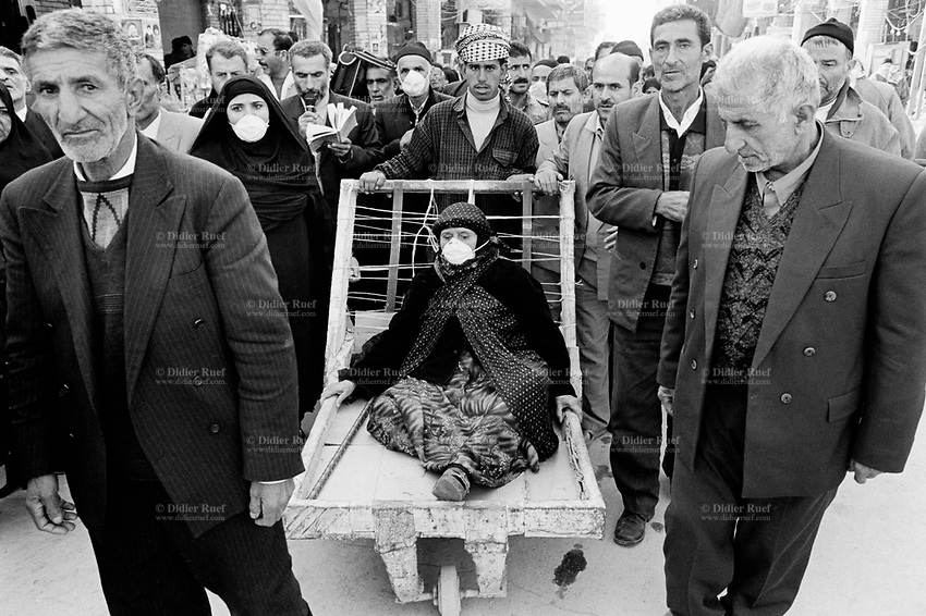Iraq. Najaf. A group of iranians pilgrims (men and women) on their way to the Holy Shrine of Imam Ali. An old woman wearing a hijab on her head is carried on a handcart. Other women are walking and wearing the tchador. Shias regard Ali as the first Imam and consider him and his descendants the rightful successors to Muhammad. The word hijab (or hidjab) refers to both the veil covering the head and traditionally worn by muslim women (Islamic headscarf), but also the  modest muslim styles of dress in general. A chador is an outer garment or open cloak worn by many Iranian women and female teenagers in public spaces. Wearing this garment is one possible way in which a Muslim woman can follow the Islamic dress code known as