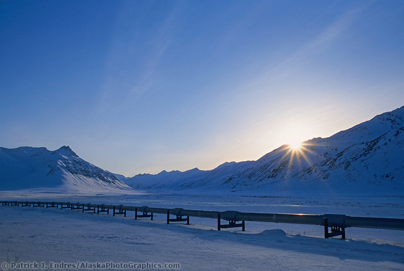 Sun sets behind the winter Brooks mountains, Trans Alaska Oil Pipeline, Alaska.