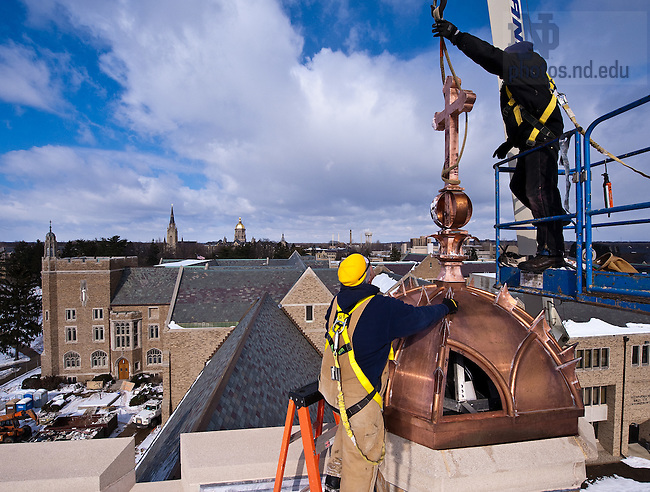 Workers install one of the four copper crosses atop the Eck Hall of Law...Photo by Matt Cashore/University of Notre Dame