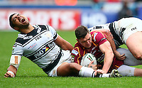 PICTURE BY VAUGHN RIDLEY/SWPIX.COM - Rugby League - Super League - Huddersfield Giants v Hull FC - Galpharm Stadium, Huddersfield, England - 09/04/12 - Hull FC's Willie Manu cries out in pain after his leg gets caught underneath Huddersfield's Danny Brough.