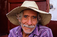 Portrait of a smiling old mexican farmer with a hat