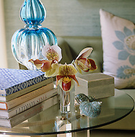 A pile of design books have been placed on a round glass side table beside a blue glass lamp in the bedroom
