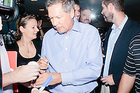 Republican presidential candidate and Ohio governor John Kasich signs autographs for people who will sell the items on eBay after a town hall campaign event at the Derry VFW in Derry, New Hampshire.