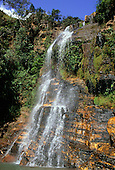 Brazil. Waterfall falling over rocky outcrop in lush valley.