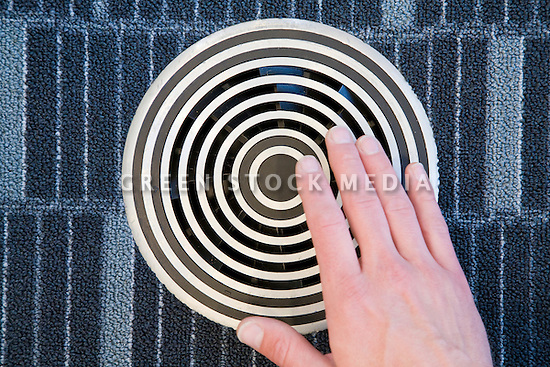 A close up of a hand over an air vent on the floor. The HVAC system utilizes an underfloor air system that distributes fresh air directly to occupants, increasing comfort and improving air quality. The system also reduces HVAC energy usage. The San Mateo Public Library integrates significant green building practices and achieved LEED Silver certification. Green features include extensive daylighting, efficient underfloor air supply, venting windows, low VOC materials, native plant landscaping, and much more. San Mateo, California, USA