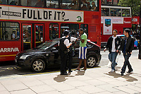 Met Police officers performing a routine MVSC moving vehicle stop check in Oxford Street, London. They are questioning the driver and occupants and examining their identification and license and insurance details..