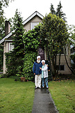 CANADA, Vancouver, British Columbia, a couple stands in front of their home in a Westside neighborhood of Vancouver, Kitsilano