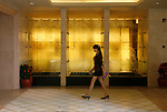 Phnom Penh's Nagaworld Casino and five-star hotel is one of Cambodia's biggest private employers with more than 3,000 staff catering for a stream of visitors. It functions non-stop 24 hours a day with an inside airconditioned controlled temperature of 21 degrees.It is a 14 storey hotel and entertainment complex, with more than 500 bedrooms, 14 restaurants and bars, 700 slot machines and 200 gambling tables. There is also a spa, karaoke and VIP suites, live bands, and a nightclub. Its monolithic building dominates the skyline at the meeting point of the Mekong and Tonle Sap rivers, in stark contrast to nearby intricate Khmer architecture.///Staff member walking past the Spa's water sculpture inside Nagaworld