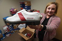 NWA Democrat-Gazette/J.T. WAMPLER Dina Rega, marketing and events coordinator at Ozark Guidance Center, shows a pair of shoes made for former Razorback coach Frank Broyles for the Masters golf tournament Thursday April 12, 2018. The shoes are an auction item along with around 2,000 pairs of shoes and 400 handbags for the center's eighth annual Walk a Mile in My Shoes sale of new and nearly new shoes and handbags at the Northwest Arkansas Holiday Inn Atrium in Springdale. The VIP pre-sale is at 5:30 today ((Friday)), and doors open to sale at 6:30 p.m. The event continues tomorrow ((Saturday)) from 8-11 a.m. Tickets are available at the door or by visiting the center's website at http://www.ozarkguidance.org/