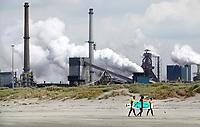 Nederland -  Velsen - 2019.    Tata Steel, de vroegere Hoogovens. Surfers op de voorgrond.   Foto Berlinda van Dam / Hollandse Hoogte
