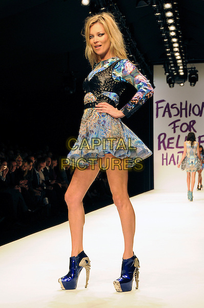 KATE MOSS.The Fashion For Relief Haiti 2010 show for London Fashion Week Autumn/Winter 2010 at Somerset House, London, England..February 18th, 2010.LFW catwalk runway full length blue beige pattern print mini dress leather corset ankle boots silver platform shoes hand on hip side.CAP/CAS.©Bob Cass/Capital Pictures.