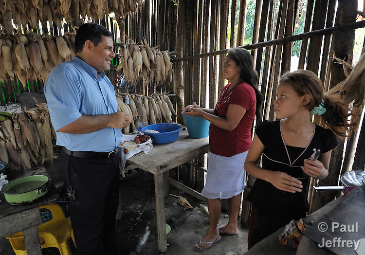 The Rev. Juan Guerrero, a native of Colombia, is a United Methodist missionary and superintendent of the church's mission in Honduras. Here he visits with Vicky Quintanilla as she makes tortillas in her home in the northern Honduran village of Ceibita.