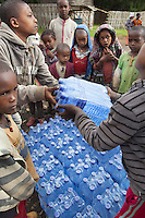 Ethiopia. Southern Nations, Nationalities, and Peoples' Region. Omo Valley. Hayzo Village. High altitude: 2800 meters. Dorze tribe. Boys and girls and plenty of six packs of mineral water. The boottles of mineral water are for sale to visiting tourists. The Dorze are a small ethnic group inhabiting the Gamo Gofa Zone who speak the Dorze language, an Omotic tongue. The Dorze are predominantly agriculturalists living in permanent villages. Well known cotton weavers, the Dorze tribe were once warriors. The Dorze numbered 40'000 reside in villages near the cities of Chencha and Arba Minch. Southern Nations, Nationalities, and Peoples' Region (often abbreviated as SNNPR) is one of the nine ethnic divisions of Ethiopia. 6.11.15 © 2015 Didier Ruef