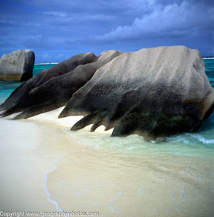 Granite boulders shaped by sea sandy beach stormy sky, Anse Source d'Argent, La Digue island, Seychelles