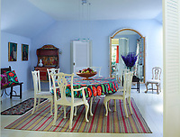 A white table and chairs stands on a striped rug in the centre of the blue dining room.