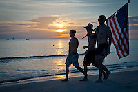 Teens walk beach carrying American flag before the fireworks show at historic Naples Fishing Pier along Gulf of Mexico, Naples, Florida, USA, July 4, 2011. Photo by Debi Pittman Wilkey