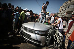 "Palestinians inspect a car that was targeted in an Israeli air strike in Gaza City on June 27, 2014. An Israeli air strike killed two Palestinian militants and critically wounded a third in the Gaza Strip on Friday, the military and Palestinian medical officials said. The attack was on a car travelling along a coastal road near a beach refugee camp in Gaza, witnesses said. One source identified the men as belonging to the Popular Resistance Committees, a network of militant groups that has fired rockets into southern Israel. The Israeli military said the men targeted had been ""involved in firing at Israel in recent weeks and were planning serious terror attacks against Israeli residents"". Photo by Ali Jadallah"