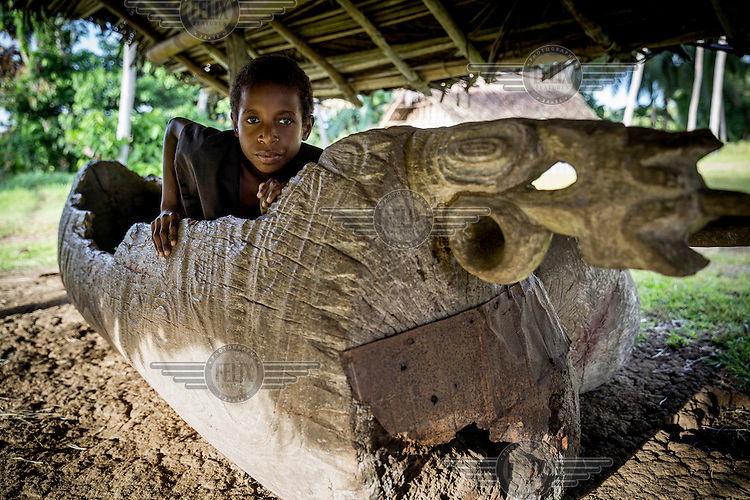Piesen Henri, 10, sits inside a 'karamut', a traditional musical instrument played during celebrations.