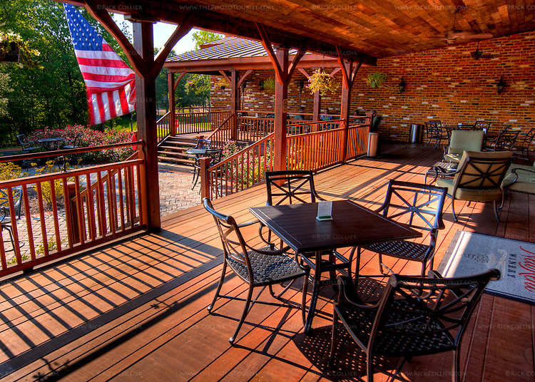 The back porch at New Kent Winery offers a number of seating options in the shade under ceiling fans.  A patio is also available just beyond the porch, with shaded tables overlooking the surrounding gardens and vineyards.  (HDR image)