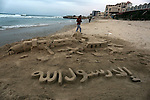 A Palestinian man creates a sand sculpture read ''Except Prophet Mohammed'' at the beach of Gaza city, January 15, 2015 in protest against insulting of the prophet Mohammed. Issued first issue of French satirical weekly Charlie Hebdo since Islamist gunmen killed 12 people in an attack on its offices during the session of questions to the governement, at the national assembly in Paris. Photo by Yasser Qudih