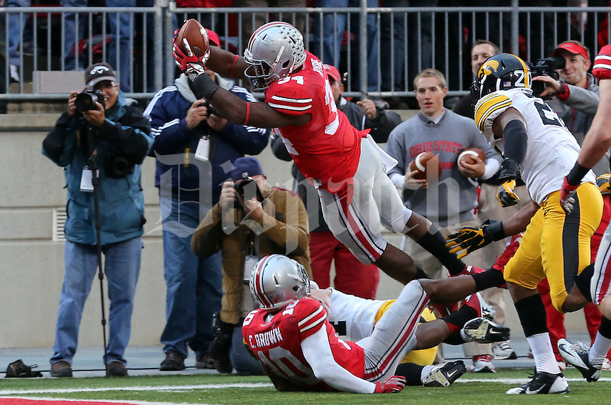 Ohio State Buckeyes running back Carlos Hyde (34) leaps for a touchdown in the fourth quarter of their game at Ohio Stadium in Columbus, Ohio on October 19, 2013. Columbus Dispatch photo by Brooke LaValley)